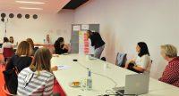 Sieben Frauen sitzen um einen Workshoptisch, auf dem ein Laptop steht, Quelle: DTF