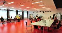 Blick in einen großen Raum, in dem drei Workshoptische stehen, an denen Menschen diskutieren, Quelle: DTF