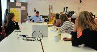 sieben Männer und Frauen sitzen um einen Workshoptisch, auf dem ein Laptop steht., Quelle: DTF