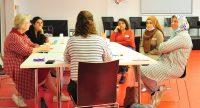 Sechs Frauen mit und ohne Kopftuch sitzen um einen Workshoptisch im Gespräch, Quelle: DTF