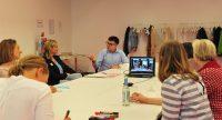 Sechs Männer und Frauen sitzen um einen Workshoptisch im Gespräch, auf dem Tisch steht ein Laptop, Quelle: DTF