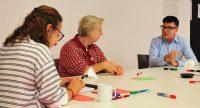 Zwei Frauen und ein Mann sitzen an einem Tisch nebeneinander im Gespräch, auf dem Tisch liegen Stifte und Papier, Quelle: DTF