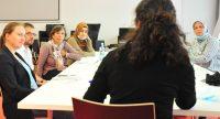 Sechs Männer und Frauen sitze um einen Workshoptisch im Gespräch, Quelle: DTF
