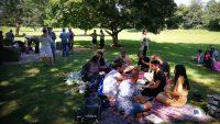 Zwei große Menschengruppen picknicken auf einer Wiese, im Hintergrund ist ein großer Baum zu sehen, einige Personen stehen., Quelle: DTF Stuttgart