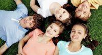 Jungen und Mädchen liegen nebeneinander auf einer Wiese, Quelle: Canva