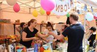 Zwei Frauen stehen hinter einem bunten Marktstand mit Ballons und Geschenken und agieren mit einem Kunden, Quelle: DTF
