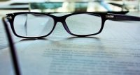 Auf einem Tisch liegen eine Brille und einige Blätter beschriebenes Papier, Quelle: Unsplash