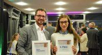Mann und junge Frau halten lächelnd zwei Preis-Plaketten in den Händen, Quelle: DTF