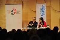 Autor im Gespräch mit Moderatorin auf der Bühne. Sitzendes Publikum ist von hinten zu sehen, Quelle: DTF Stuttgart