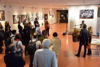 Eine Person steht am Pult und spricht zum stehenden Publikum, an den Wänden hängen Bilder, Quelle: DTF Stuttgart