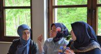 Drei Frauen mit Kopftüchern sitzen vor einem Fenster ins Grüne und unterhalten sich., Quelle: DTF