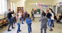 Eine Gruppe Kinder und junger Frauen stehen im Kreis in einem Klassenzimmer und tanzen, Quelle: DTF