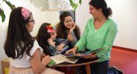 Eine Frau liest für drei Mädchen ein Buch vor, Quelle: DTF Stuttgart