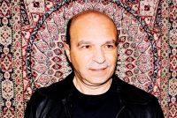 Der Musiker Ozan Ata Canani steht vor einem bunten Teppich., Quelle: Ozan Ata Canani