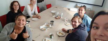 DTF-Team im Besprechungsraum isst zusammen Strudel