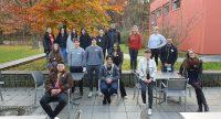 Die Projektteilnehmer*innen sitzen auf Stühlen und stehen dahinter. Sie stehen vor dem Tagungshaus., Quelle: DTF