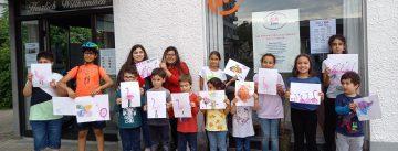 Vierzehn Kinder stehen vor dem Eingang des Kafem und halten ihre gemalten Flamingo-Bilder in die Kamera.