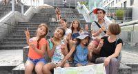 Fröhliche Kinder mit Eis und einer Stadtteilkarte sitzen auf einer Treppe, Quelle: DTF
