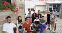 Gruppenbild mit jungen Menschen auf der Terrasse einer Weinstube, Quelle: DTF