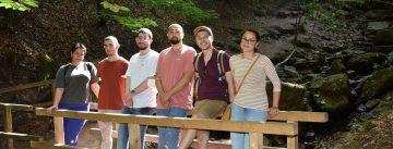 Junge Menschen stehen auf einer Brücke im Wald