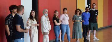 Gruppenbild mit jungen Menschen, die an einer Wand nebeneinander stehen