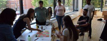 Workshopteilnehmer*innen stehen um einen Tisch mit Bastelmaterial