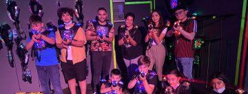 Kinder und junge Erwachsene stehen mit Lasertag-Pistolen in einem dunklen Raum