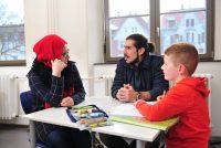Eine Frau mit rotem Kopftuch, ein junger Mann mit Zopf und ein Junge sitzen um einen Tisch, auf dem ein Heft und eine Federmappe liegen., Quelle: DTF
