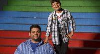Junger Mann und Junge stehen nebeneinander auf einer Treppe und lächeln., Quelle: DTF