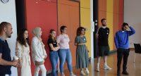 Junge Leute in sommerlicher Kleidung stehen nebeneinander vor einer bunten Wand, Quelle: DTF