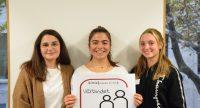 Drei junge Frauen stehen nebeneinander und lächeln, eine hält ein Schild, Quelle: DTF