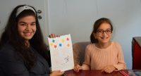 Junge Frau und Mädchen sitzen lächelnd nebeneinander am Tisch, die Frau hält einen Kalender hoch, Quelle: DTF