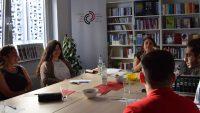 junge Menschen sitzen rund um einen Besprechungstisch und unterhalten sich lachend, Quelle: DTF