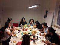 junge Menschen sitzen in der DTF Geschäftsstelle rund um einen bedeckten Tisch und essen zusammen, Quelle: DTF