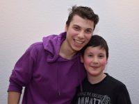 junger Mann in freundschaftlicher Umarmung mit einem Jungen, beide lächeln in die Kamera, Quelle: DTF