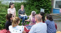 Acht Personen sitzen im Freien um eine Sitzbank herum und unterhalten sich, Quelle: DTF Stuttgart