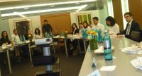 junge Menschen sitzen an Besprechungstischen, im Platz zwischen den Tischen ist ein Beamer, Quelle: DTF