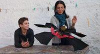Junge lehnt sich lächelnd an einem Holztisch, junge Frau rechts neben ihm hält einen Vampir aus einem Regenschirm gebastelt, Quelle: DTF