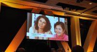 Übertragung eines Videos mit junger Frau und Mädchen an einer orange beleuchteten Wand, Quelle: DTF