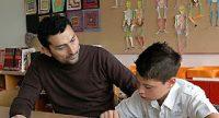 junger Mann und Junge schauen gemeinsam in ein Arbeitsheft, sie sitzen in einem Schulzimmer, Quelle: DTF