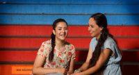 zwei junge Frauen sitzen lachend auf einer blauroten Treppe, Quelle: DTF