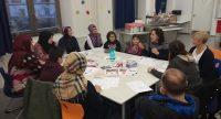Eltern und Kinder sitzen versammelt rund um einen weißen Tisch voller Infomaterialien, Quelle: DTF