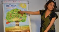 """Frau deutet auf ein Plakat mit dem Bild eines Baumes und dem Satz """"Kinder wachsen"""", Quelle: DTF"""