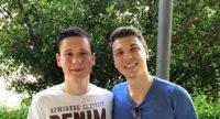 zwei junge Männer lächeln in die Kamera, sie stehen in kurzer Hose in einem Außenbereich, Quelle: DTF