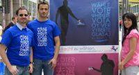 zwei Männer in blauen T-Shirts neben blauem und pinken Wahlposter, links von ihnen ist eine Frau im pinken T-Shirt, Quelle: DTF