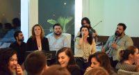 Kleine Bühne mit singender Frau und Bandmitgliedern. Im Publikum eine Gruppe aus sechs Personen, die lachen, Quelle: DTF Stuttgart