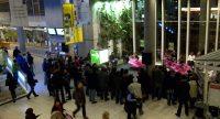 Stehendes Publikum, die sich eine Tanzshow von Tänzerinnen anschaut. Dahinter vorbeilaufende Menschen., Quelle: DTF Stuttgart