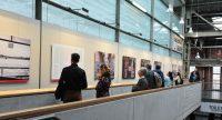 Menschen stehen entlang einer Empore und betrachten die ausgestellten Bilder., Quelle: DTF Stuttgart