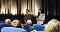 Publikum schaut auf zwei Frauen, die sich vor der Kinoleinwand mit dem Publikum unterhalten., Quelle: DTF Stuttgart
