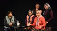 Szene eines Theaterspiels mit drei Frauen, die an einem Tisch sitzen und zwei weiteren stehenden Frauen. Alle hören einer sprechenden Frau zu., Quelle: DTF Stuttgart